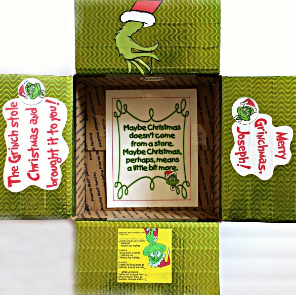The Grinch Care Package Box decorated with shiny, green duct tape and Grinch graphics.