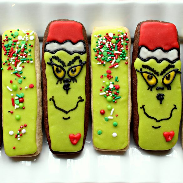 Two Grinch cookie sticks and two green sprinkled cookie sticks on a white plate.