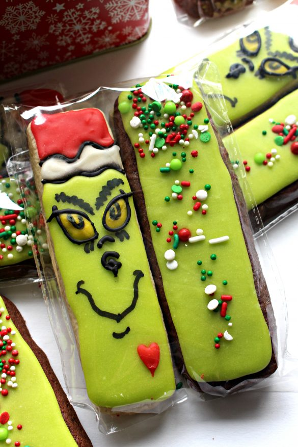 A pair of Decorated Grinch Cookies enclosed in a cellophane bag for gifting.