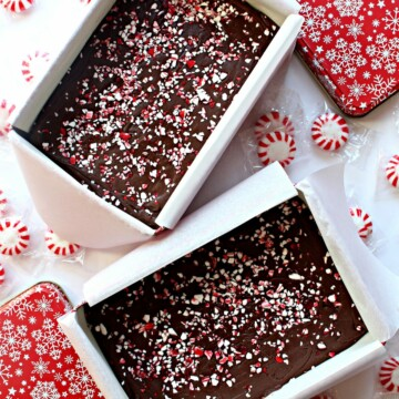 Two open tins filled with Peppermint Fudge, next to the red and white lids.