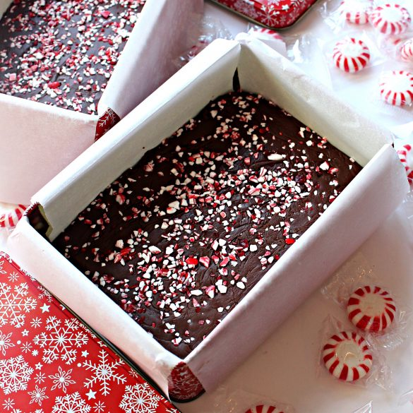 A parchment paper lined gift tin filled with fudge and topped with crushed candy canes