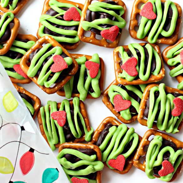 Grinch Pretzels topped with chocolate, green zigzags and a red heart.