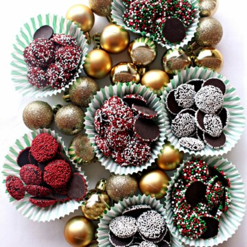 Gold ball ornaments and cups of Nonpareil chocolate candies coated in different colored sprinkles.
