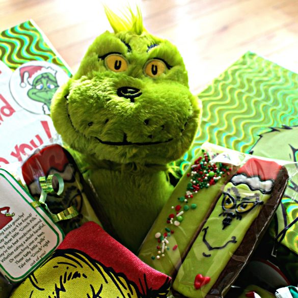Stuffed green Grinch inside the corner of a care package.