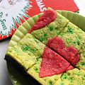 Green Grinch Brownies with a red heart in the middle, on a green plate with The Grinch book in the background