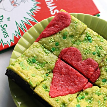 Green Grinch Brownies with a red heart on top on a green plate next to book.