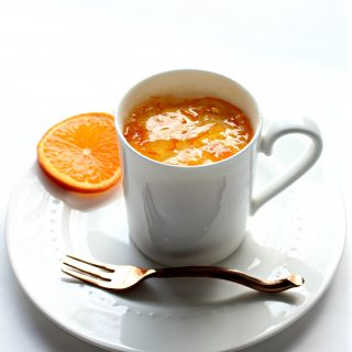 Orange Mug Cake in white mug on plate