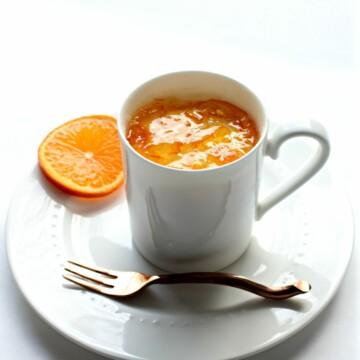 Orange Mug Cake in white mug on plate