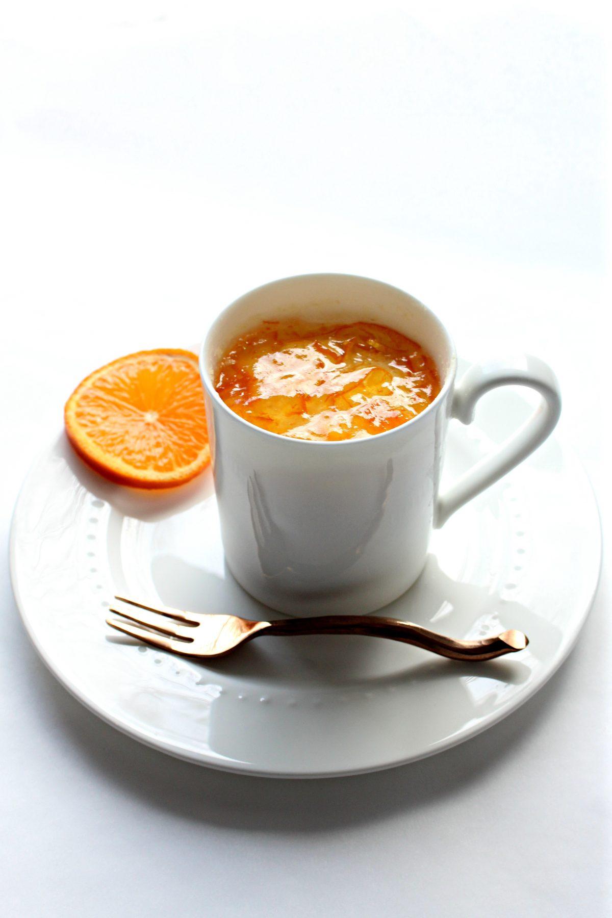 Orange Mug Cake topped with marmalade in white mug on plate with slice of orange.