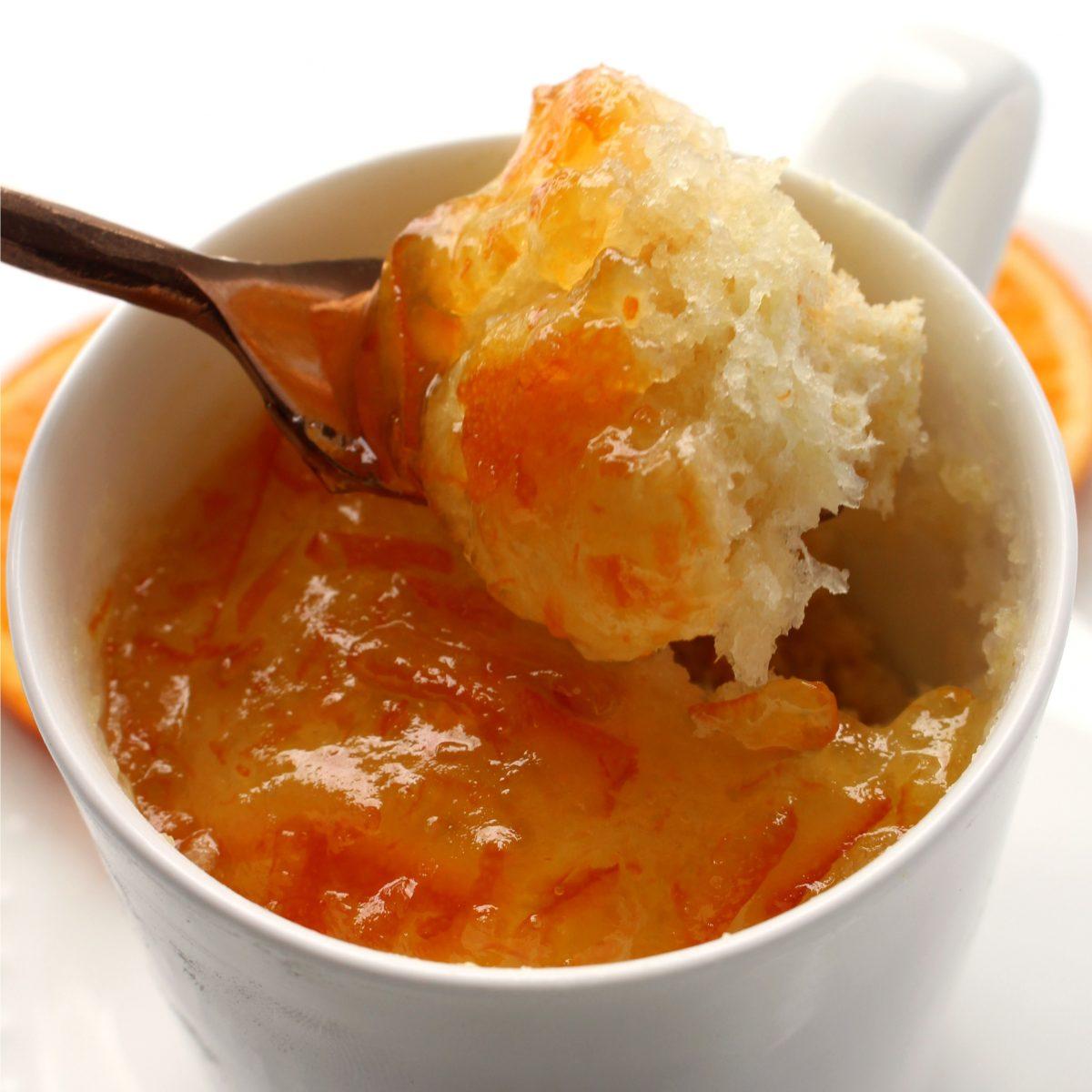 Close up marmalade topped mug cake with a piece of cake on a fork.