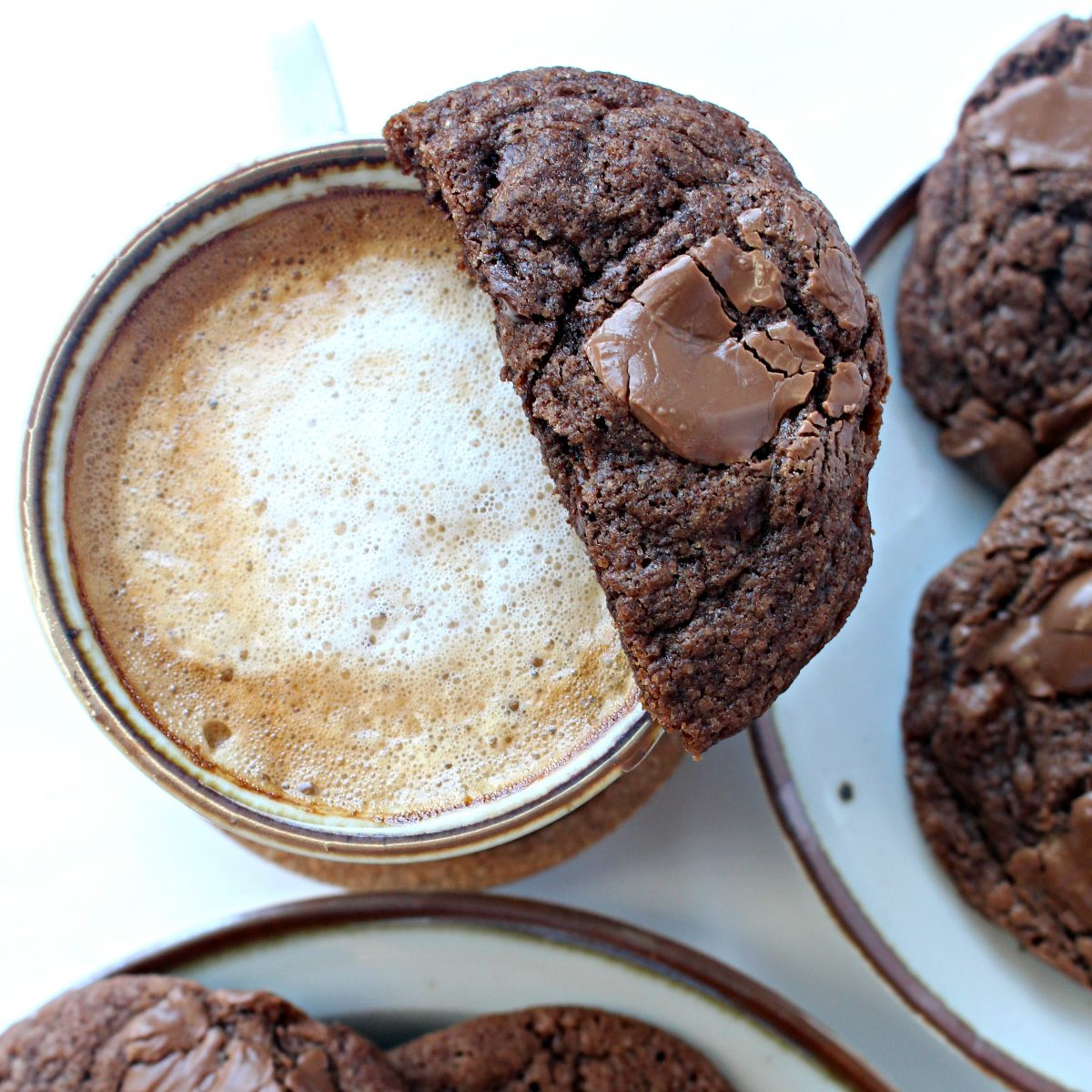 Half dark chocolate cookie balanced on rim of coffee cup.