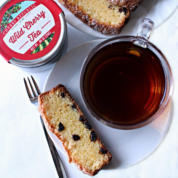 Cup of tea with a slice of cake and the tea tin