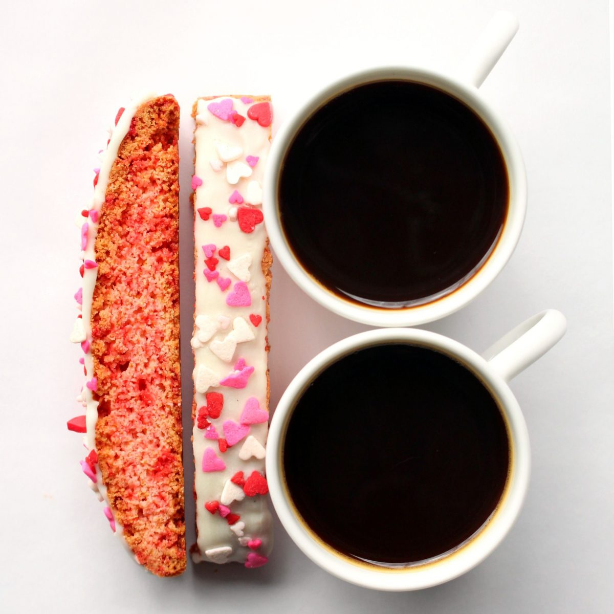 Two biscotti decorated on top with white chocolate and heart sprinkles, next to two espresso mugs.