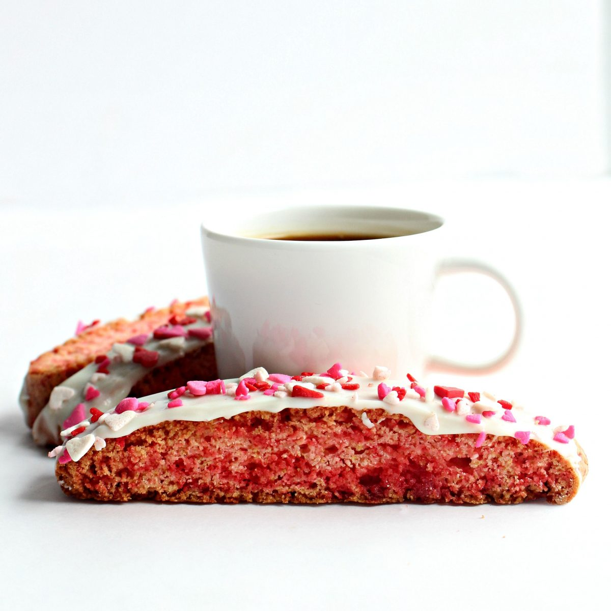 Pink biscotti topped with white chocolate and sprinkles in front of espresso mug.