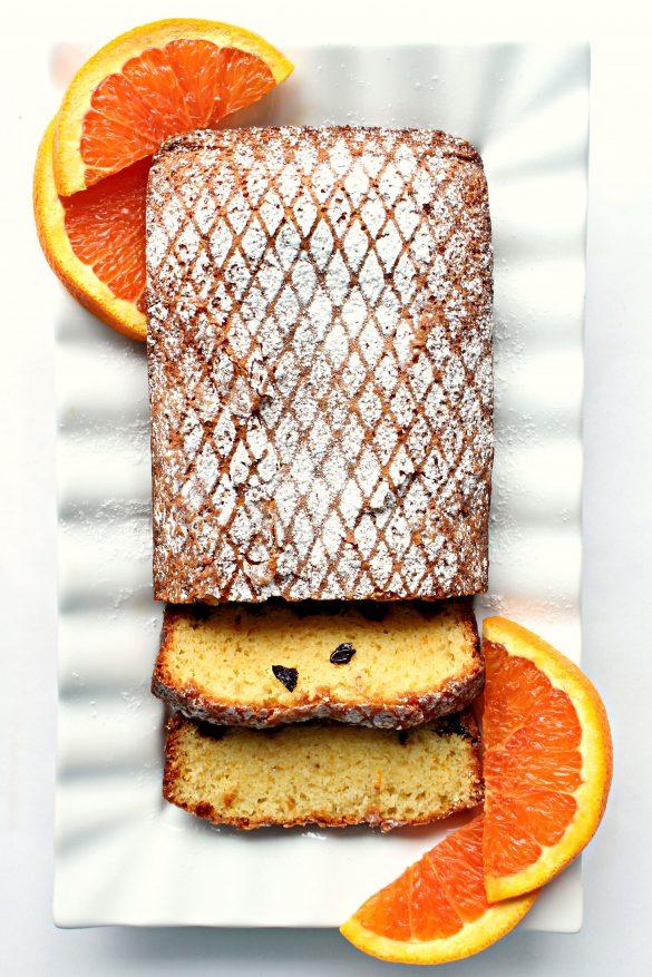 Orange Olive Oil Cake on platter with orange slices