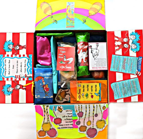 "The inside of the care package with the flaps of the box decorated from Seuss books. The top flap has a rainbow and two hot air balloon from ""oh the places you will go"". Two side flaps are red and white stripes with Thing 1 and 2 from Cat in the Hat. The bottom flap has Truffula trees from The Lorax. Inside the box the gifts are wrapped in bright colors with mini copies of Seuss book covers taped on each"