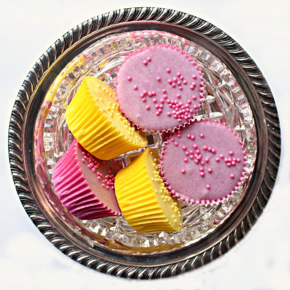 Purple and yellow peanut butter cups in a crystal candy dish