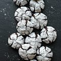 Chocolate Crinkle Cookies covered in confectioners sugar on a slate background.