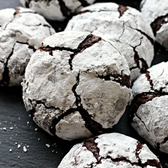 Closeup of Chocolate Crinkle Cookie coated in confectioners sugar with chocolate showing through the cracks.