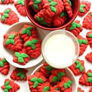 Red strawberry shaped cookies with green leaves on plates and a bowl with a glass of milk