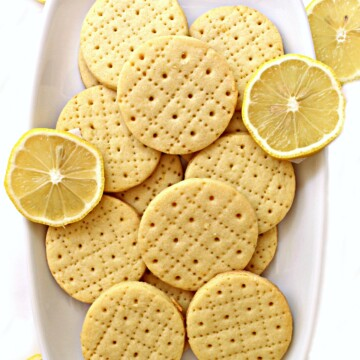 Shrewsbury Biscuits on a white platter with a few slices of lemon