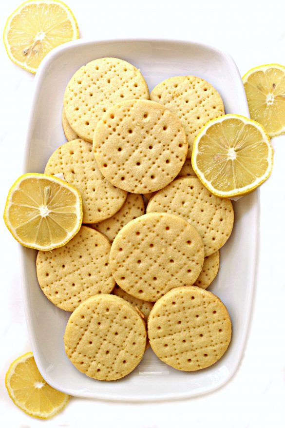 Shrewsbury cookies on a white platter with a few slices of lemon