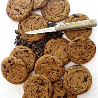 Round, brown Chocolate Chip Molasses Cookies on a white background with a small knife and chopped chocolate