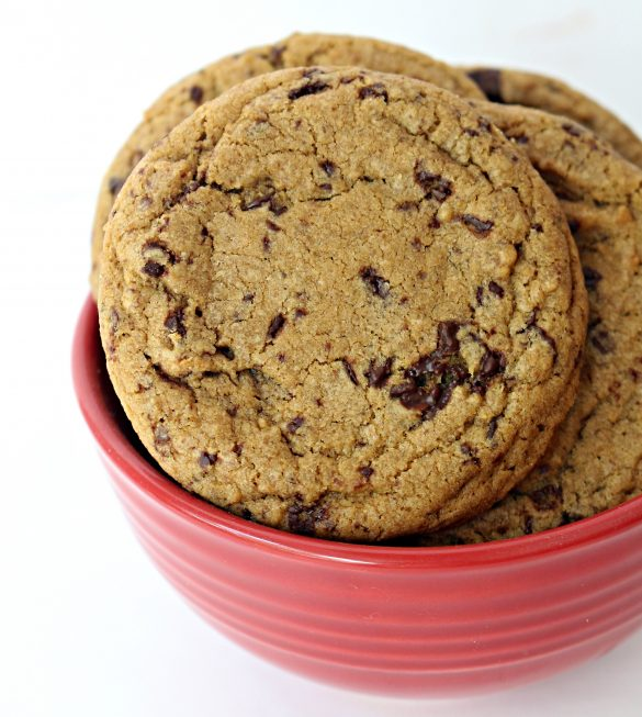 Closeup of a brown, chocolate speckled Chocolate Chip Molasses Cookie in a red bowl