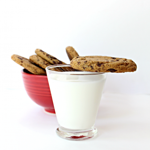 Thick edge of a Chocolate Chip Molasses Cookie balanced on the rim of a clear glass of milk in front of a red bowl filled with more cookies