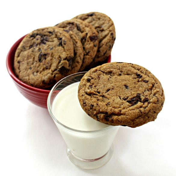 one Chocolate Chip Molasses Cookie on the rim of a clear glass of milk with 4 cookies in a red bowl in the background