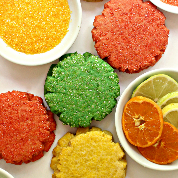 orange, green, yellow Mexican Sugar Cookies and white bowls with yellow sugar and sliced citrus fruit