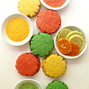 sugar cookies on white background with white bowls of colored sugar and sliced citrus fruit