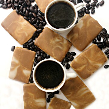 Coffee Cookies with brown and white marbled icing on a white background with coffee beans and 2 white mugs of espresso