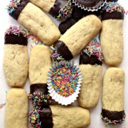 Oatmeal Shortbread fingers with one end of each dipped in chocolate and sprinkles on a white background