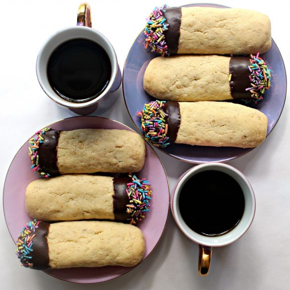 Two mugs of coffee and two plates each with 3 Oatmeal Shortbread Cookies dipped in chocolate and pastel sprinkles