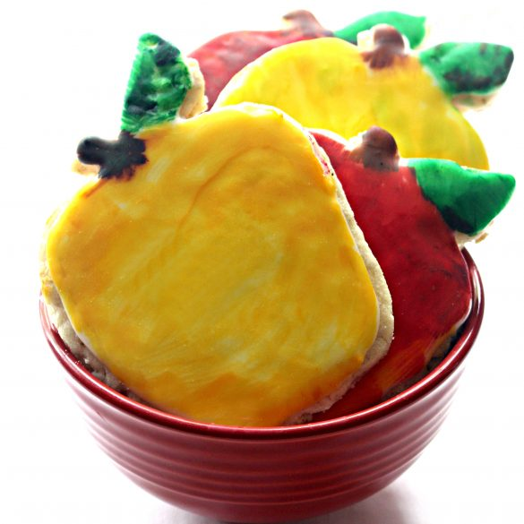 Apple Oatmeal Cutout Cookies iced yellow and red in a red bowl