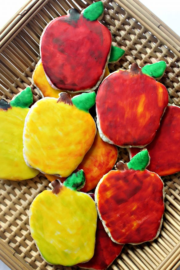 Apple Oatmeal Cutout Cookies painted red and yellow with food coloring in a shallow woven basket