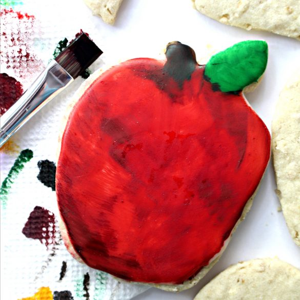 A paint brush next to a cookie painted red shows the watercolor look from painting food coloring onto the apple shaped cookie