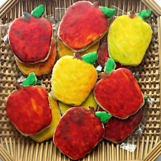 red and yellow apple shaped cookies in a brown woven basket tray