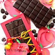 Unmolded chocolate bar next to chocolate bar inside red gift box surrounded by red apple shaped gift tags