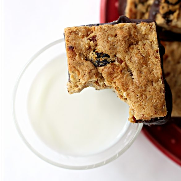 closeup of oatmeal fruit bar on rim of glass of milk