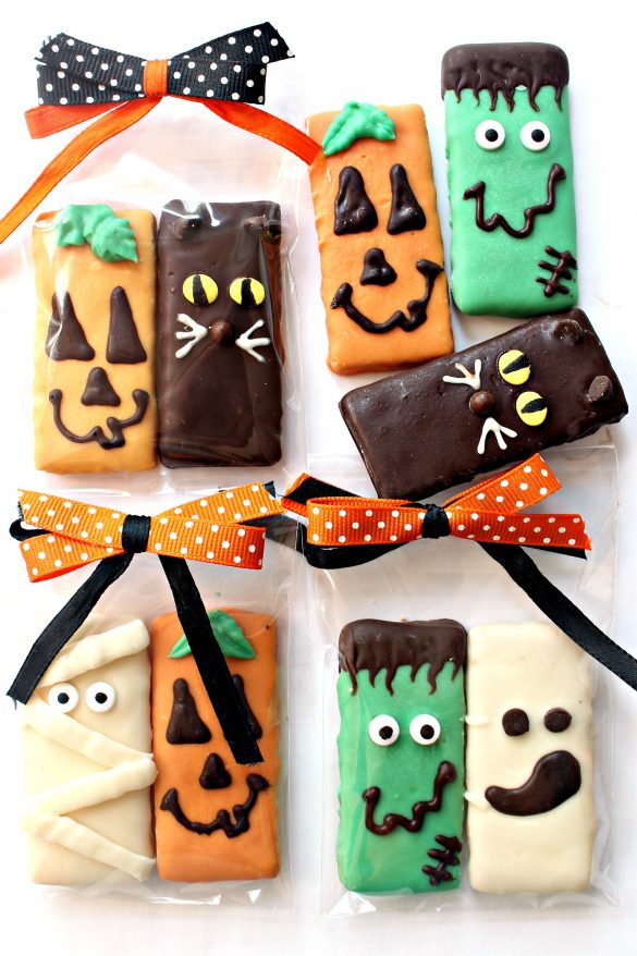 Spooky Graham Crackers coated in chocolate and decorated as pumpkins, cats, Frankenstein, ghosts, and mummies packaged in clear plastic bags with orange and black bows.