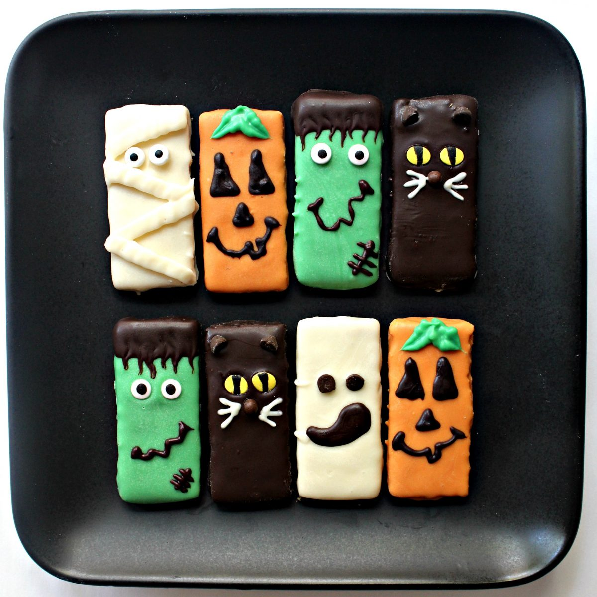 Chocolate coated graham Crackers decorated as Halloween characters on a black plate.