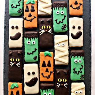 Spooky Graham Crackers coated in chocolate and decorated as Frankenstein, Pumpkin, Ghost, Mummy, and Cat.
