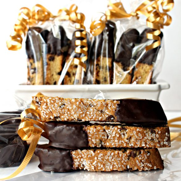 3 Chocolate Chip Biscotti piled in front of wrapped biscotti showing the sparkle sugar on top and chocolate dipped ends