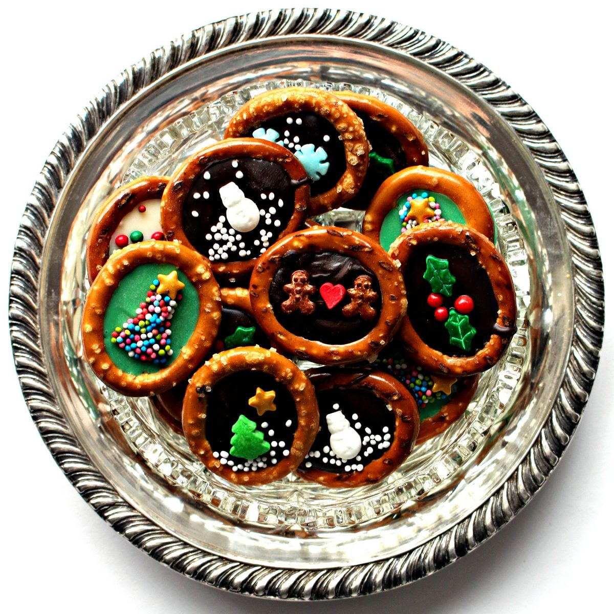 Pretzel rings with chocolate centers and sprinkle designs on a round silver platter.