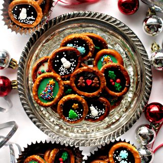 Christmas Pretzels with chocolate centers and sprinkle designs in foil cupcake liners and in a crystal candy dish with silver and red ribbon and ornaments.