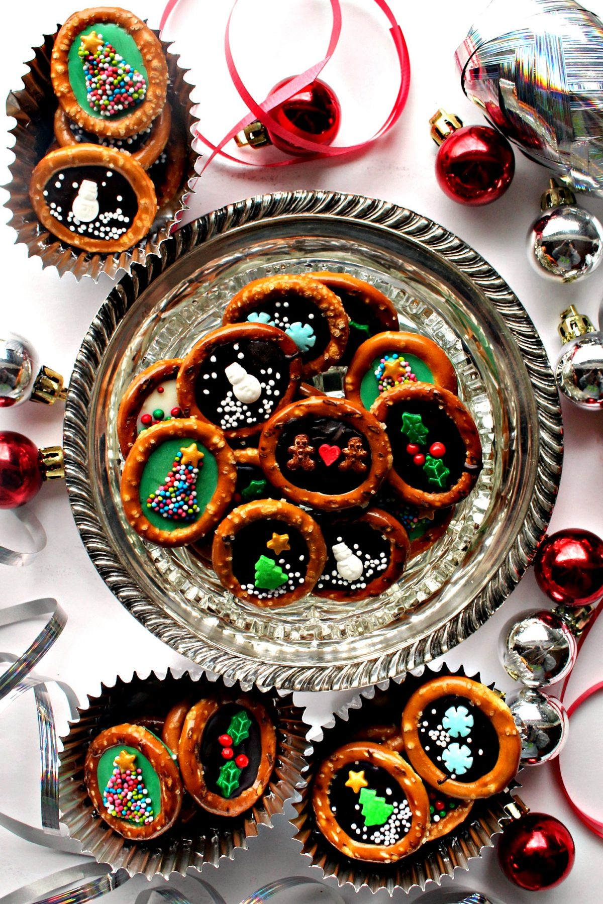 Pretzel rings with chocolate centers and sprinkle designs on a silver tray.