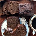 Dark brown Gingerbread Loaf Cake sliced and slices on a plate