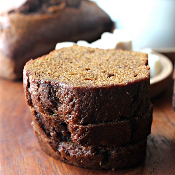 Three thick slices of Gingerbread Loaf Cake in a stack showing the moist shiny crust